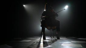 A menina joga a composição no violoncelo no assoalho é folhas dispersadas com notas Silhueta Fundo preto do fumo filme