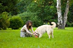A menina joga a esfera com um cão imagem de stock