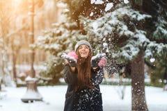 A menina joga a neve acima na cidade foto de stock