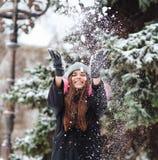 A menina joga a neve acima na cidade imagem de stock royalty free