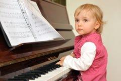 A menina joga o piano Foto de Stock Royalty Free