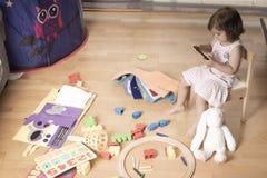 A menina joga o telefone celular A menina é enganchada ao telefone celular Não joga com brinquedos O telefone celular é mau para  imagem de stock
