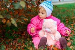 A menina joga um urso do brinquedo foto de stock royalty free
