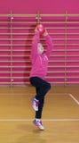 A menina joga uma bola vermelha na cesta Imagens de Stock Royalty Free
