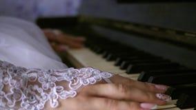 A menina joga uma parte musical no piano Close-up os dedos f?meas jogam um instrumento musical do teclado M?os de uma menina filme