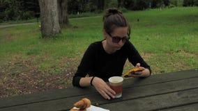 menina 4k bonita na camisa longa feito a mão preta da luva e nos óculos de sol marrons verdes que sentam-se na tabela de madeira  filme