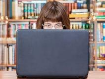 A menina lê da tela do portátil na biblioteca Imagens de Stock