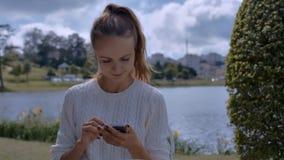 A menina lê a letra em sorrisos de IPhone no banco de rio video estoque