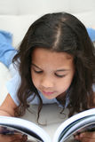 A menina lê o livro foto de stock