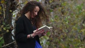 A menina lê o livro cativando, velha escola, tecnologia tradicional video estoque
