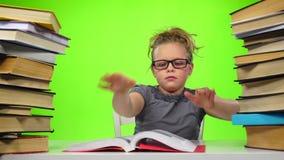 A menina lê o livro fecha-o e toma-a outro Tela verde Movimento lento vídeos de arquivo