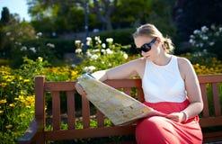 A menina lê o mapa ao ar livre Fotografia de Stock Royalty Free