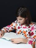 A menina lê um livro Fotografia de Stock Royalty Free