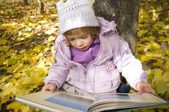 A menina lê um livro Imagem de Stock Royalty Free