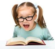 A menina lê um livro ao desgastar vidros foto de stock