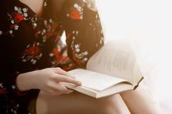 A menina lê um livro interessante Fotografia de Stock Royalty Free