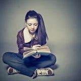 A menina lê um livro Fotos de Stock Royalty Free