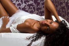 Menina Latin que sorri em bedsheets Fotografia de Stock Royalty Free