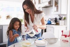 Menina latino-americano nova que faz o bolo na cozinha com ajuda de seu mum, cintura acima imagem de stock