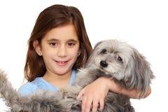 Menina latino-americano que abraça seu cão isolado em w Imagem de Stock Royalty Free