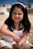 Menina latino-americano que constrói uma areia   Fotos de Stock