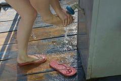 A menina lava seus pés e mãos sob a água pouco chuveiro na rua fotos de stock royalty free