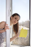 A menina lava uma janela Fotos de Stock