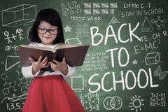 A menina leu um livro na frente do quadro-negro Imagens de Stock