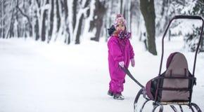 A menina leva um trenó no parque, uma criança independente imagem de stock
