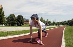 A menina levanta e estica seus pés na pista de atletismo Fotos de Stock