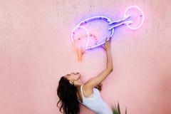A menina levanta na parede cor-de-rosa, fingindo beber de um vidro feito dos tubos de néon unidos à parede foto de stock