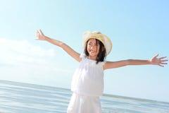 A menina levanta suas mãos de encontro ao céu azul Foto de Stock