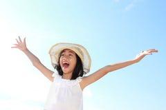 A menina levanta suas mãos de encontro ao céu azul Imagem de Stock
