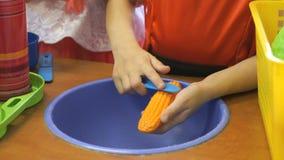 A menina limpa a cenoura vermelha artificial video estoque