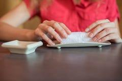 A menina limpa suas mãos com uma toalha quente rolada em um rolo dentro Fotos de Stock Royalty Free