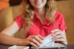 A menina limpa suas mãos com uma toalha quente rolada em um rolo dentro Imagens de Stock