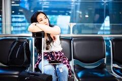 A menina lindo do viajante senta-se em uma cadeira no aeroporto Woma bonito fotos de stock