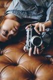 Menina lindo que encontra-se no sofá de couro com a câmera da foto em suas mãos Imagem de Stock Royalty Free