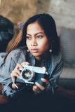 Menina lindo que encontra-se no sofá de couro com a câmera da foto em suas mãos Fotos de Stock Royalty Free