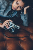 Menina lindo que encontra-se no sofá de couro com a câmera da foto em suas mãos Imagem de Stock