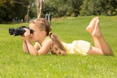 Menina Lokking nos binóculos Fotografia de Stock