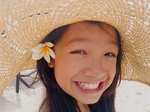 A menina longa asiática do cabelo preto está vestindo o chapéu de palha e a flor branca Imagens de Stock