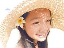 A menina longa asiática do cabelo preto está vestindo o chapéu de palha e a flor branca Fotos de Stock Royalty Free