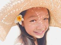 A menina longa asiática do cabelo preto está vestindo o chapéu de palha e a flor branca Fotos de Stock