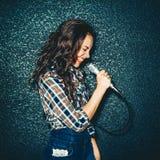 Menina louca que guarda o microfone e o sorriso Bonito atrativo Foto de Stock Royalty Free