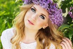 Menina loura adolescente com a grinalda das flores lilás Fotografia de Stock Royalty Free