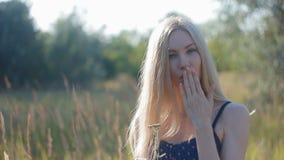 A menina loura agradável envia um beijo que guarda a flor em suas mãos video estoque