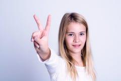 Menina loura agradável que mostra o sinal da vitória Imagens de Stock