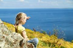 Menina loura agradável que senta-se na costa de um lago e que olha na distância Fotos de Stock