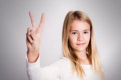 Menina loura agradável que mostra o sinal da vitória Fotografia de Stock
